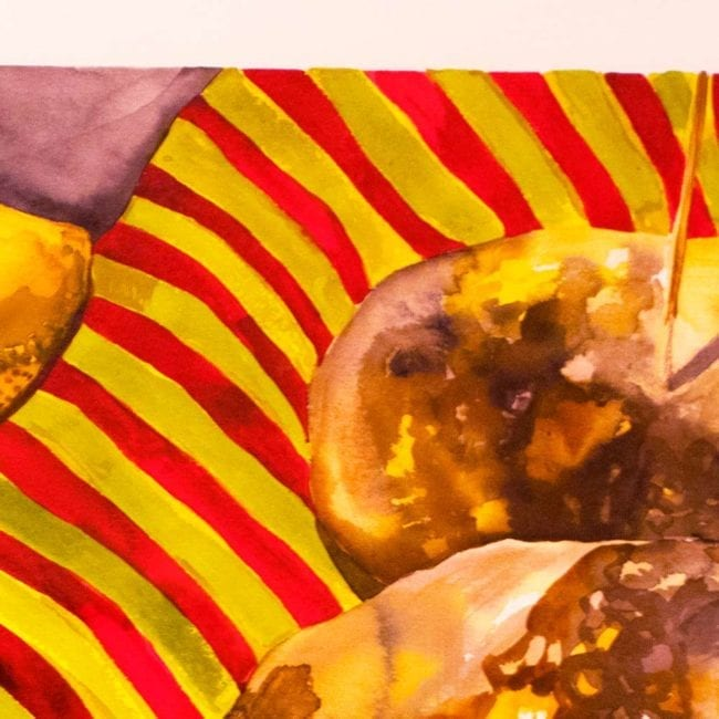 close up of the watercolor still life painting showing the end one of the quinces and the gourd as well as the yellow and red striped blanket