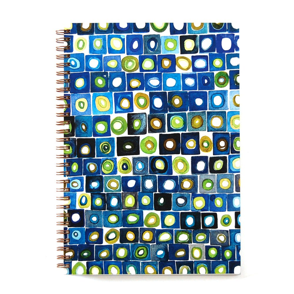 Top view of a wire bound notebook with colorful geometric pattern of blue, green and white squares with circles inside
