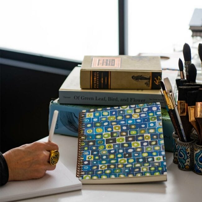 blue and green square notebook leaning against books while a writer writes near their brushes