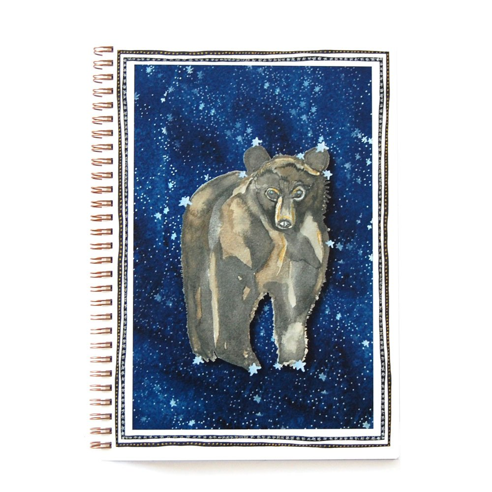 top view of a wire bound notebook with watercolor brown bear against a starry blue background