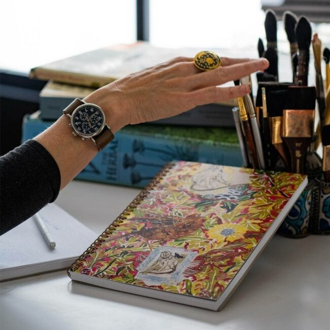 monkey king notebook with hand reaching towards a paintbrush