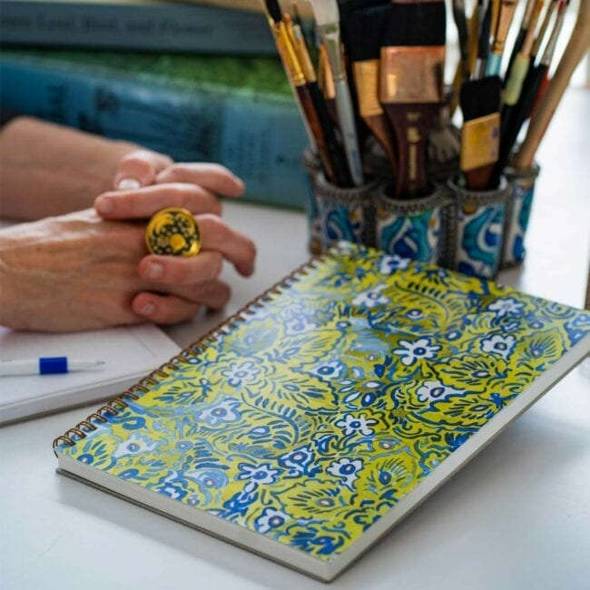 green and blue flower notebook leaning against brushes while a writer pauses