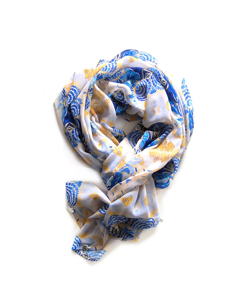 Blue, ochre and white patterned wrap in a delicate georgette fabric. Milagro charms are handsewn onto the edges of each wrap.