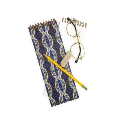 purple and yellow celestial geometric patterned long skinny notebook with a pencil eraser and glasses on top