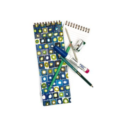 long skinny notebook with a blue, green and white watercolor cover of squares and circles, a few colored pencils and markers are on top of the notebook