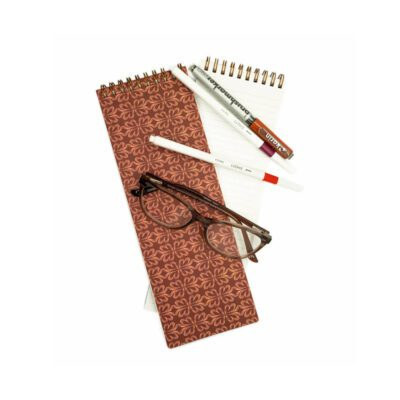 skinny notebook with red clay colored background and geometric pink cloverleaf pattern on top, glasses and pens with the notebook