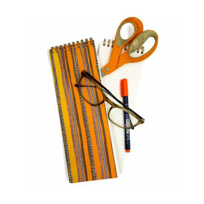 long skinny striped notebook with an orange and yellow background; purple and blue decorative stripes on top with stars and graphic elements. On top of the notebook are scissors, glasses and pens