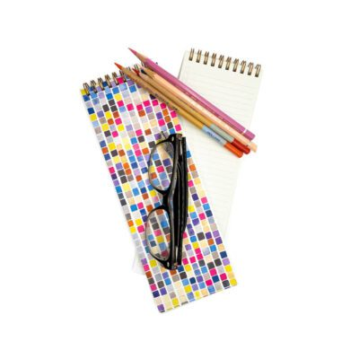 Long skinny notebook with very colorful geometric squares on the colorful, also glasses and colored pencils on top