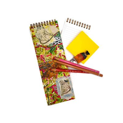 Skinny notebook with a watercolor image of monkeys, birds and jungle foliage. Notebook has colored pencils on top with yellow post it notes on the side