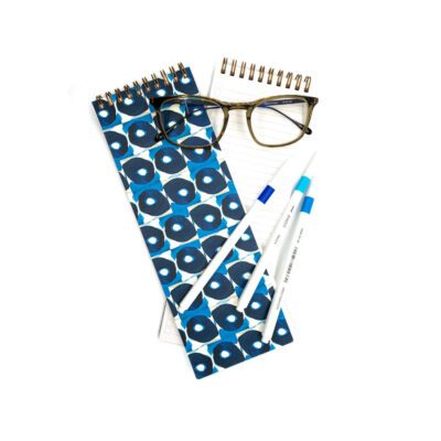 long skinny notebook with blue and white oval shaped pattern on the cover. On top of the notebooks are a pair of reading glasses and blue pens