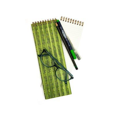 long skinny notebook with a green watercolor background and green patterned vines pattern on top. A pair of reading glasses and colored pencils lying on top.