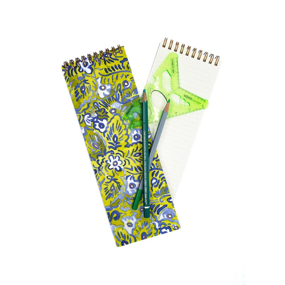 long skinny notebook with a floral watercolor pattern on top in green, blue and white. Also on top of the notebook are colored pencils and a green plastic shape stencil