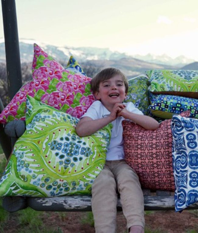young boy smiling and sitting in a hammock surrounded by lots of colorful throw pillows
