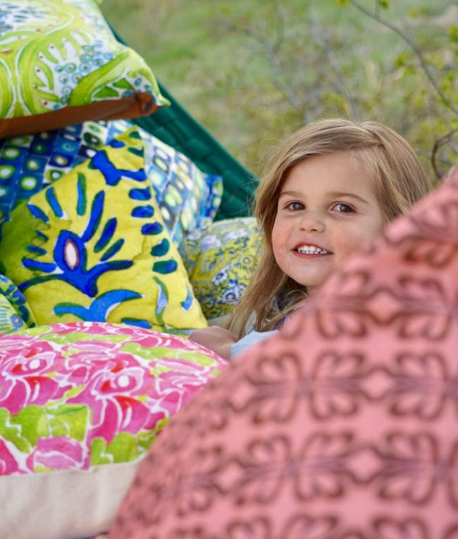 young girl smiling in a hammock surrounded by many throw pillows