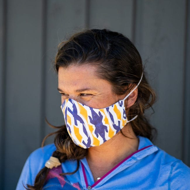 woman wearing cloth face mask with ikat purple-blue and yellow patterned face mask