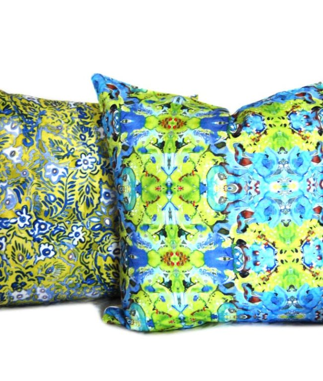 green and blue kaleidoscope abstract pattern throw pillow cover shown with another patterned throw pillow