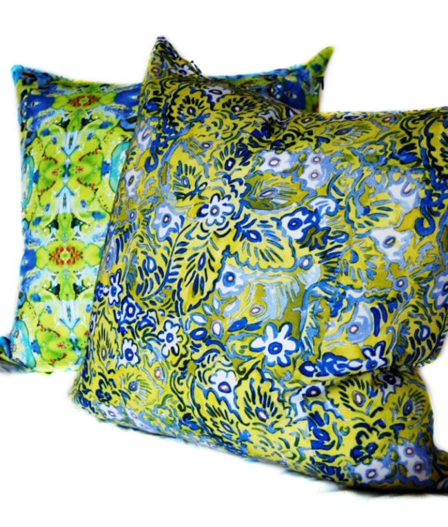 Bold green blue white floral pattern throw pillow shown with another colorful and patterned throw pillow