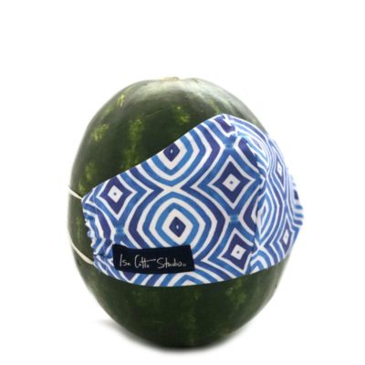 blue and white cloth face mask displayed on a watermelon