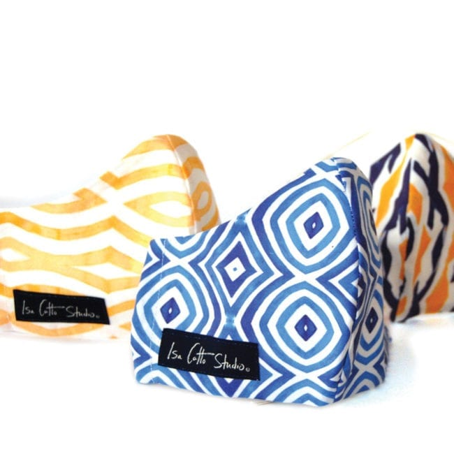 group of cloth face masks with blue and white geometric pattern in the front yellow and white geometric pattern behind and ikat blue and yellow pattern in the back