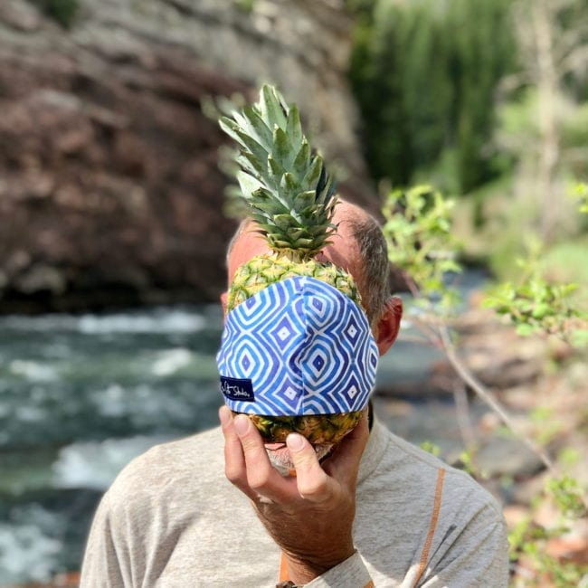 man holding pineapple with blue and white cloth face mask in front of face standing in front of a river