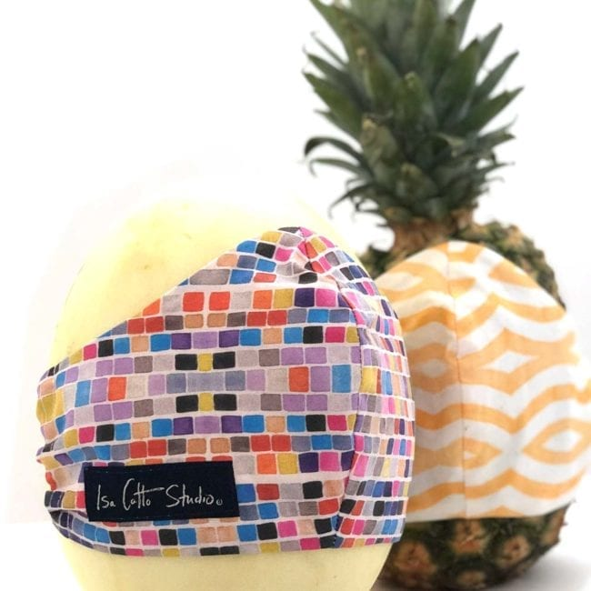 cloth face mask in geometric colorful pattern on a honeydew melon with yellow and white patterned mask on a pineapple behind