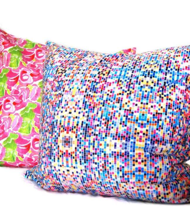 colorful square geometric pattern on a throw pillow based on eulers number shown with a rose patterned pillow in background