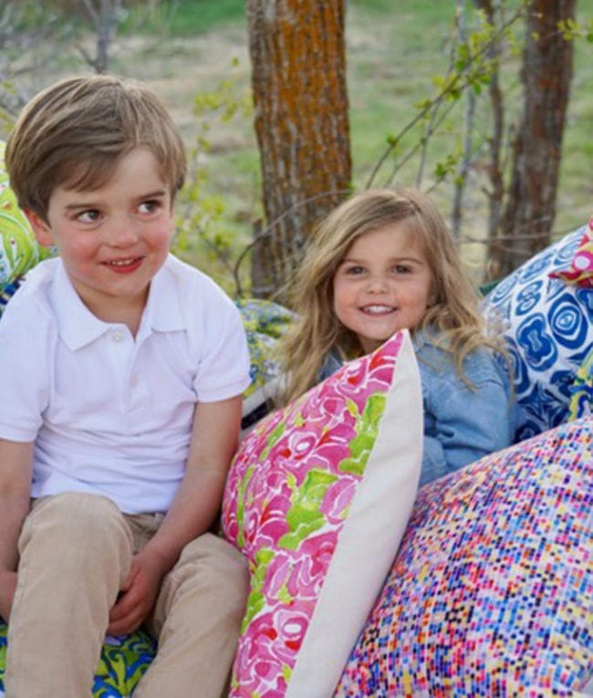 young brother and sister in hammock surrounded by piles of throw pillows