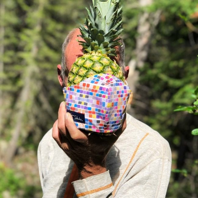 man holding pineapple in front of face with a colorful geometric square patterned face mask in front of face