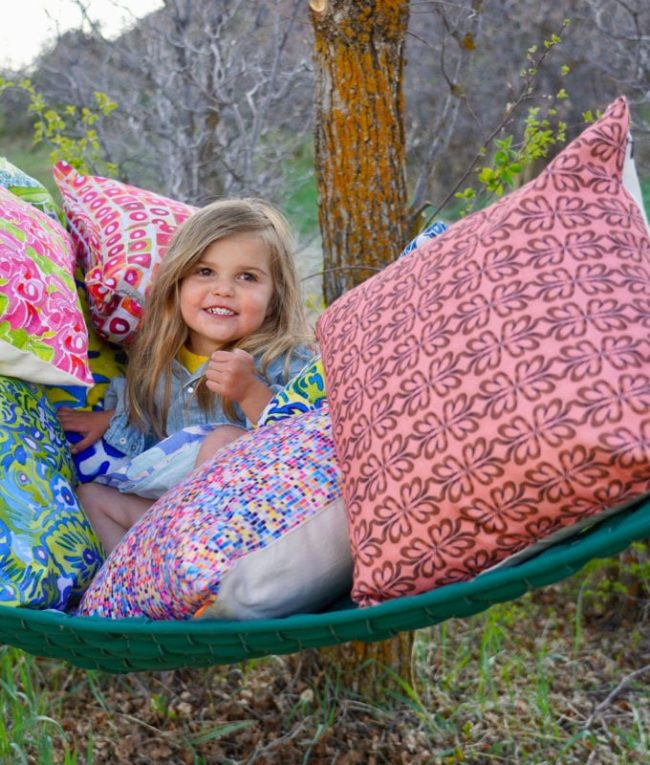 young smiling girl in hammock surrounded by lots of throw pillows