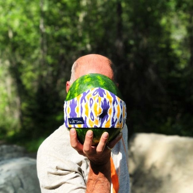 man holding watermelon in front of face with cloth face mask that has a purple-blue and yellow ikat style pattern
