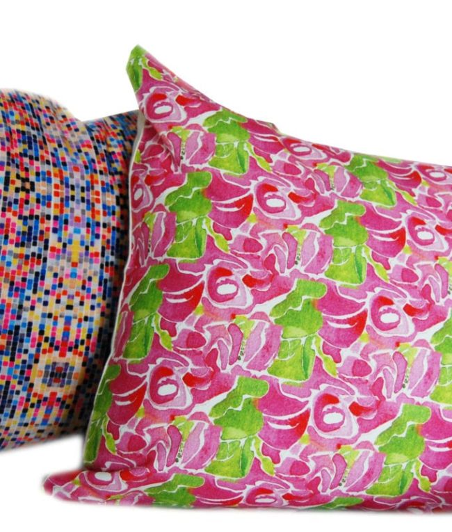 pink and green rose patterned throw pillow cover shown with a geometric pattern in the background