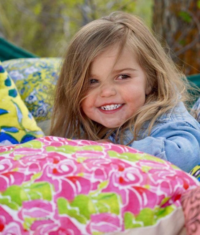 young girl smiling in a hammock surrounded by throw pillows