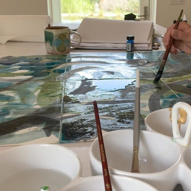 side view of isa's hand holding paintbrush working on abstract painting watercolor is pooled in the center