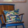 colorful geometric pillow in a modern wood rocking chair with a metal frame in bright blue