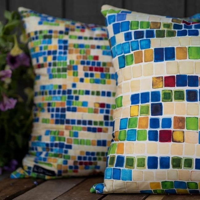 image of two pillows on a bench with basket of petunias. pillows are a colorful geometric pattern with blue, yellow and green squares and an occasional brick red square