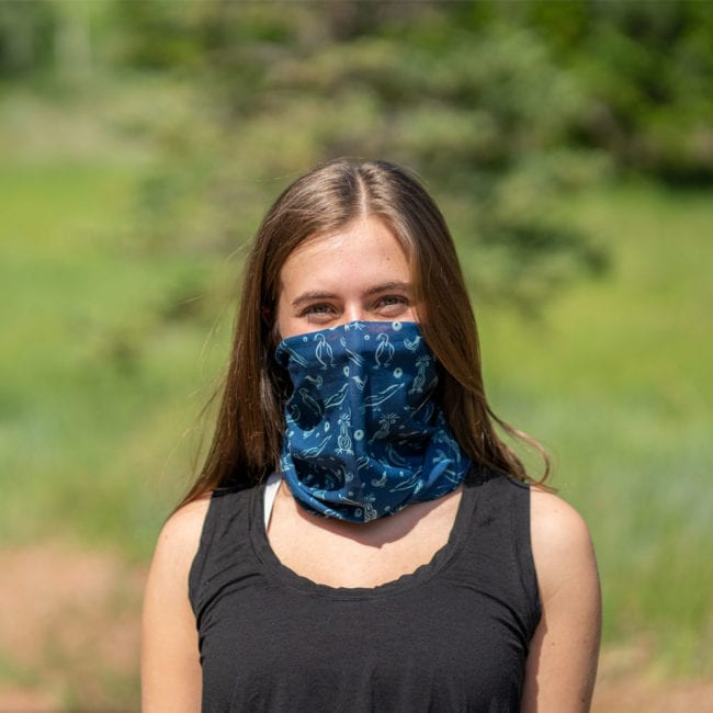 girl wearing blue and green bird and river neck tube over mouth and nose