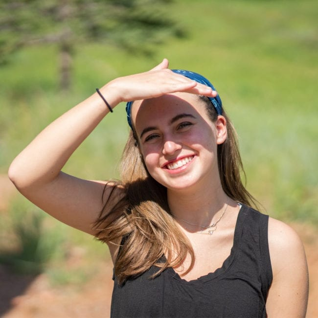 girl shading her eyes and smiling while wearing blue and green neck tube as a headband