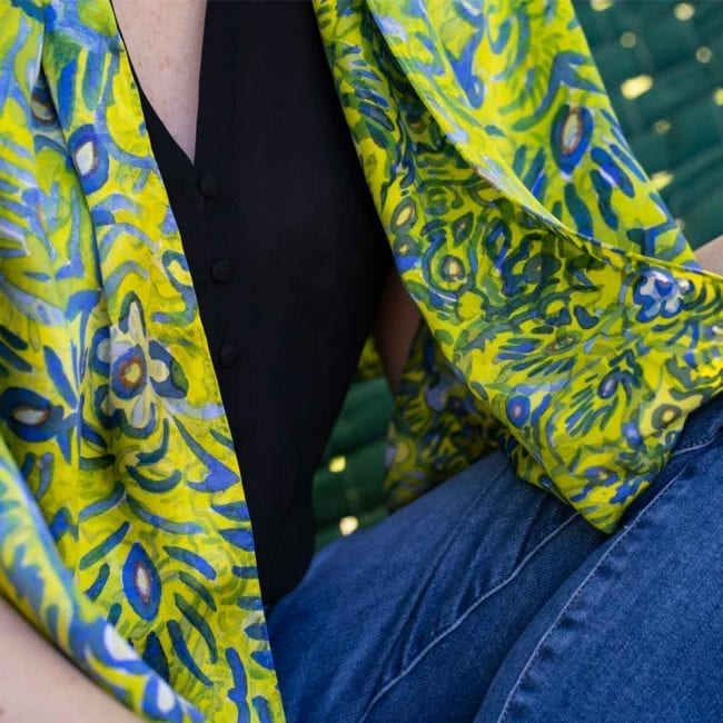 detail and blue and green floral patterned silk scarf on a woman