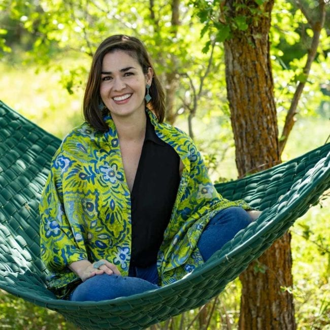 woman wearing green and blue patterned silk scarf as a shawl while sitting in a hammock