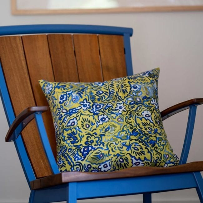 blue green and white floral patterned throw pillow on a modern wood rocking chair with a bright blue metal frame