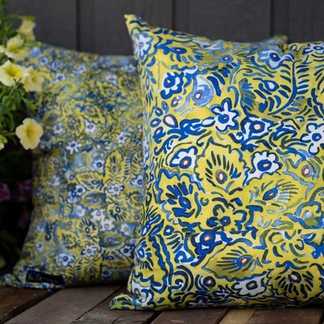 two pillows on a bench outside with petunias. foreground pillow has large blue, green and white floral pattern. pillow in background has smaller scale of the same pattern