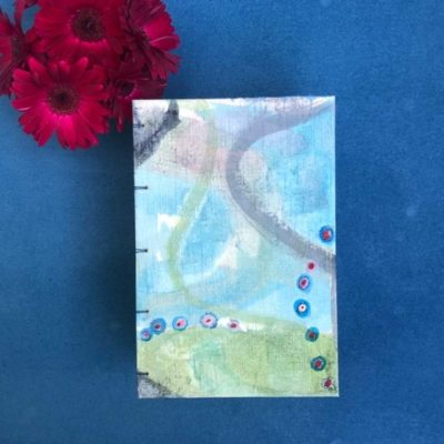 top down view of hand-painted journal with abstract blue and green background a narrow grey swath and small blue and red dots inspired by human cells shown with red gerber daisies