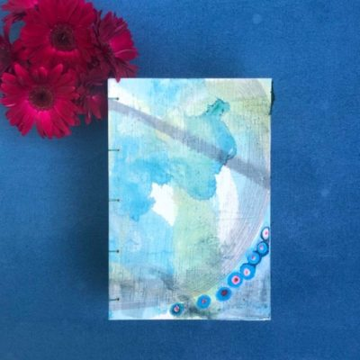 top down view of hand-painted journal cover with abstract blue and green background a narrow grey swatch across top and a band of blue and red and white dots across bottom inspired by human cells shown with dark red gerber daisies