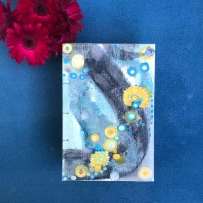 top down view of hand-painted journal abstract blue background with dark and light grey swathes across and yellow blue and white dots in varying sizes inspired by human cells shown with dark red gerber daisies