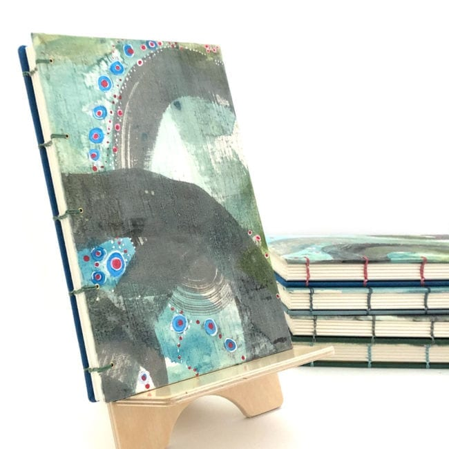 hand-painted journal with sea green and blue background and broad grey swathes red and blue dot details handsewn binding