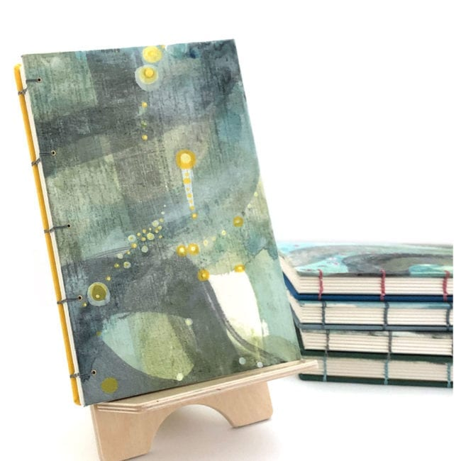 hand-painted journal with soft green and blue background and broad grey strokes with small yellow dot details abstract