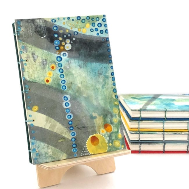 hand-painted journal with sea inspired colors in background strong grey swashes and a vertical row of blue and white dots