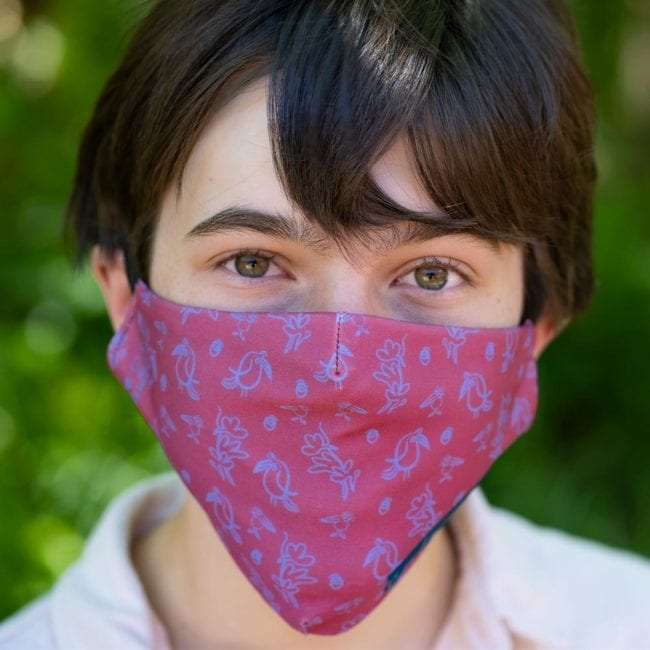 young man up close wearing face mask dark rose background with playful illustrated bird pattern in purple
