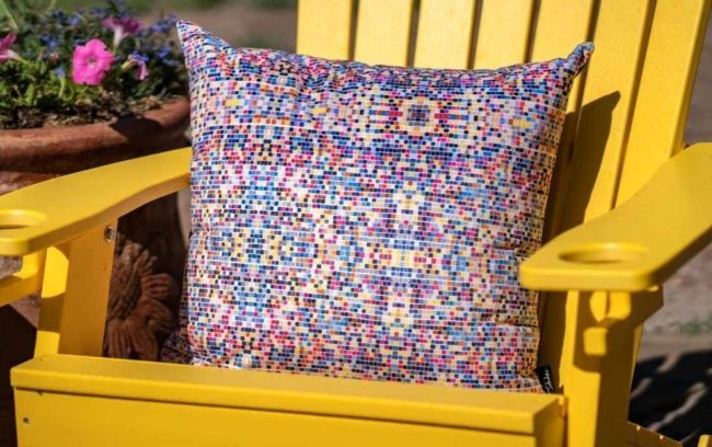 small velvet throw pillow with blue, pink, and tan squares in a yellow chair