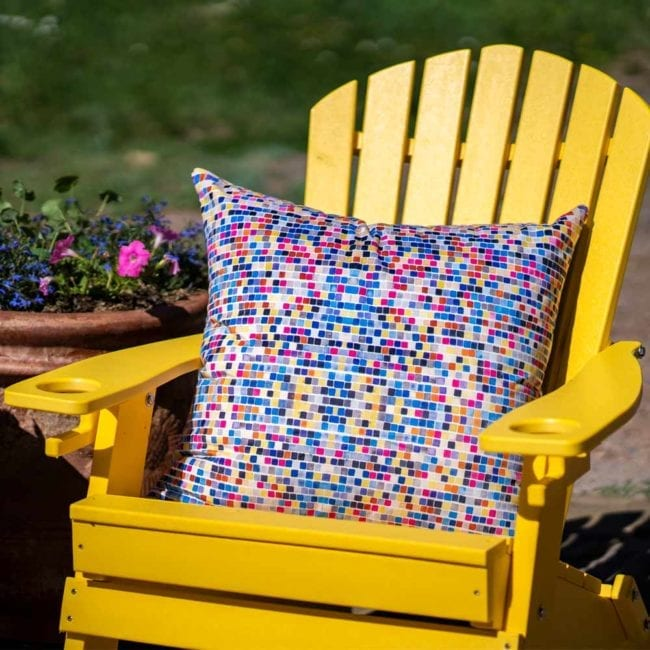 large throw pillow with blue pink and tan squares in a chair